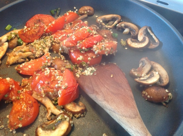 Stirring in the hemp seeds through the tomato-mushroom mix