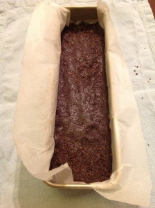 Raw Brownie crumble, pressed into the tin. I folded some of the parchment paper over and used my fingers to smooth the surface.
