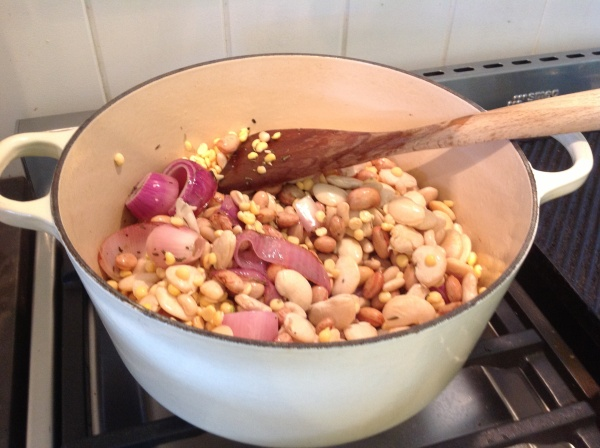 Adding the soaked white beans and split peas to the onions and garlic and herbs.
